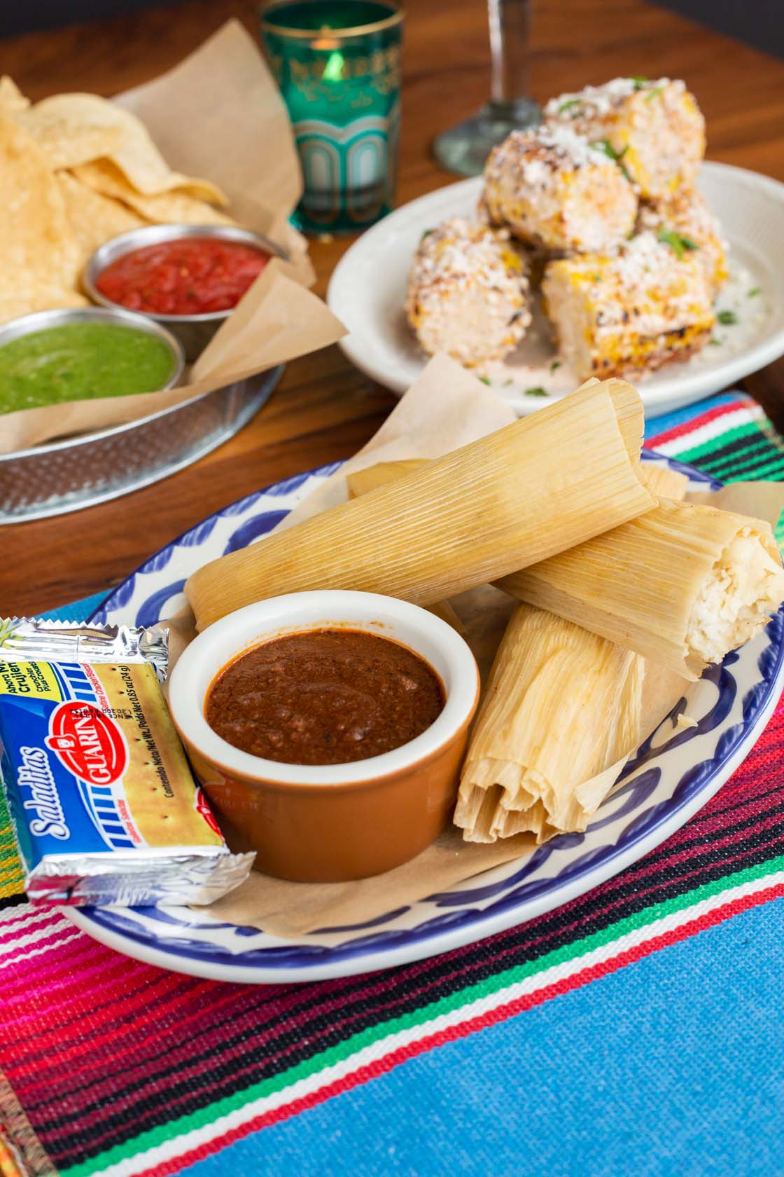Three plated tamales with chili gravy and packet of saltine crackers