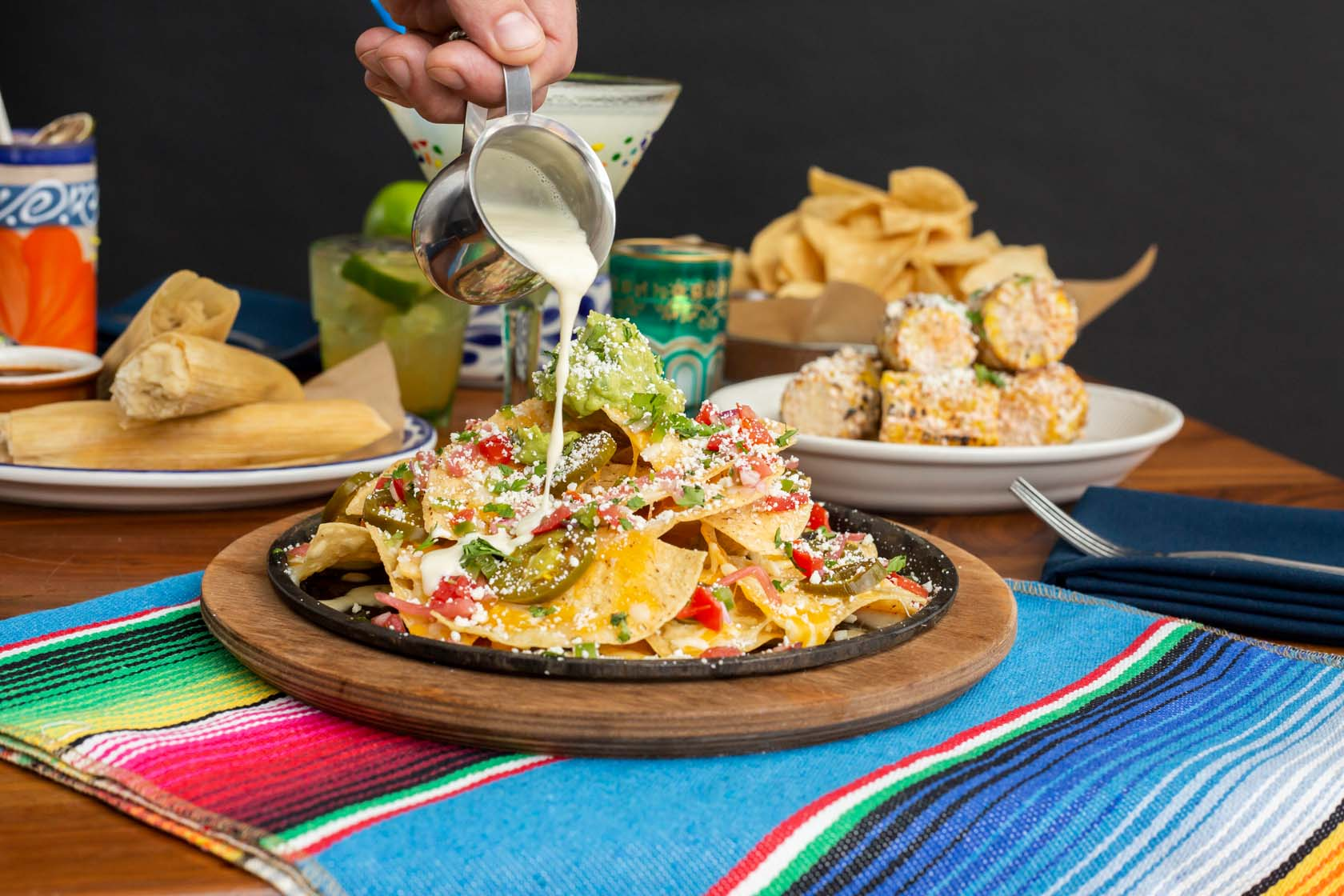 Small metal pitcher of queso sauce being drizzled over plate of nachos.