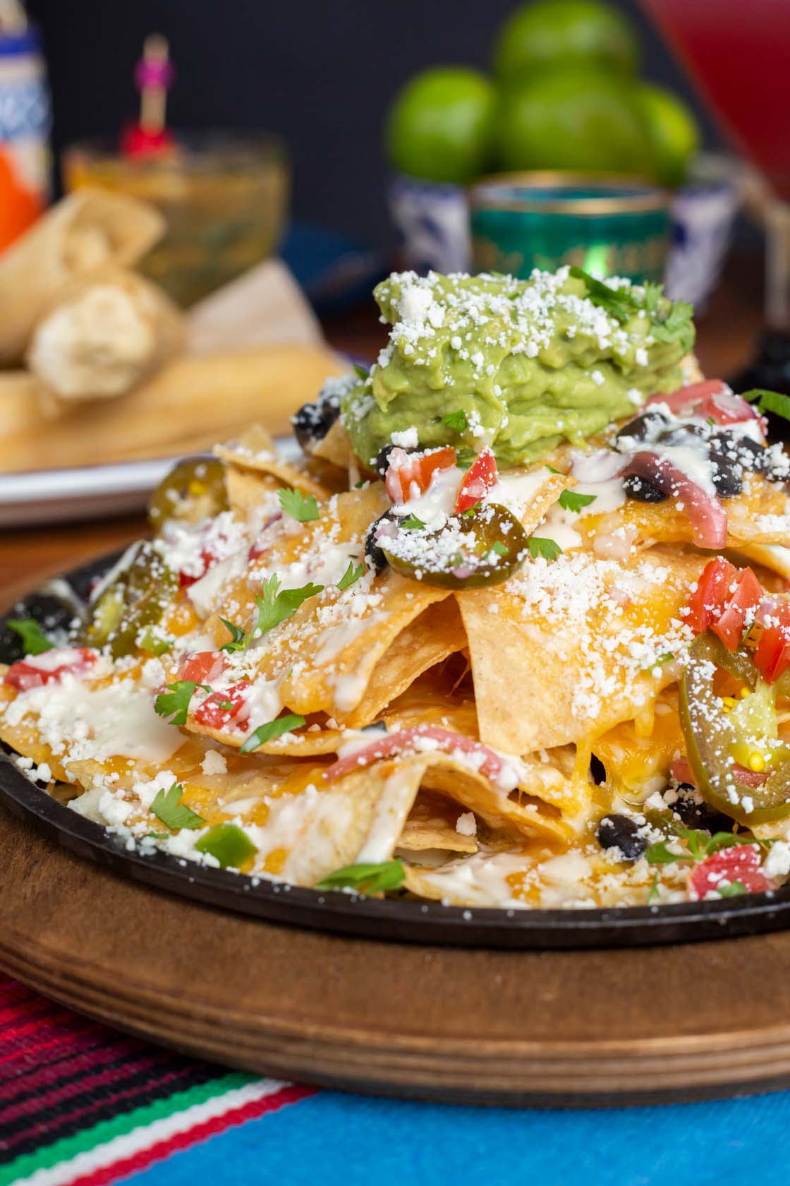 Plated nachos with dollop of guacamole on top and sliced jalapeños, tomatoes and black olives, crumbled cheese.