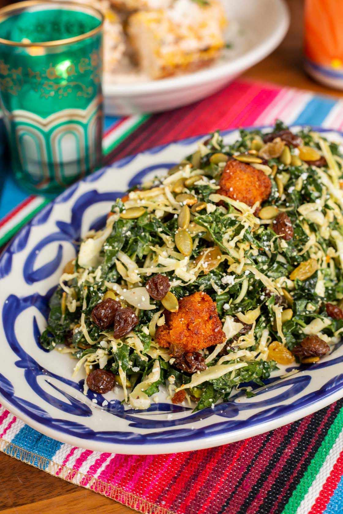 Kale salad on oval plate with cabbage, pepitas, cotija cheese, masa croutons, chimichurri yogurt dressing.