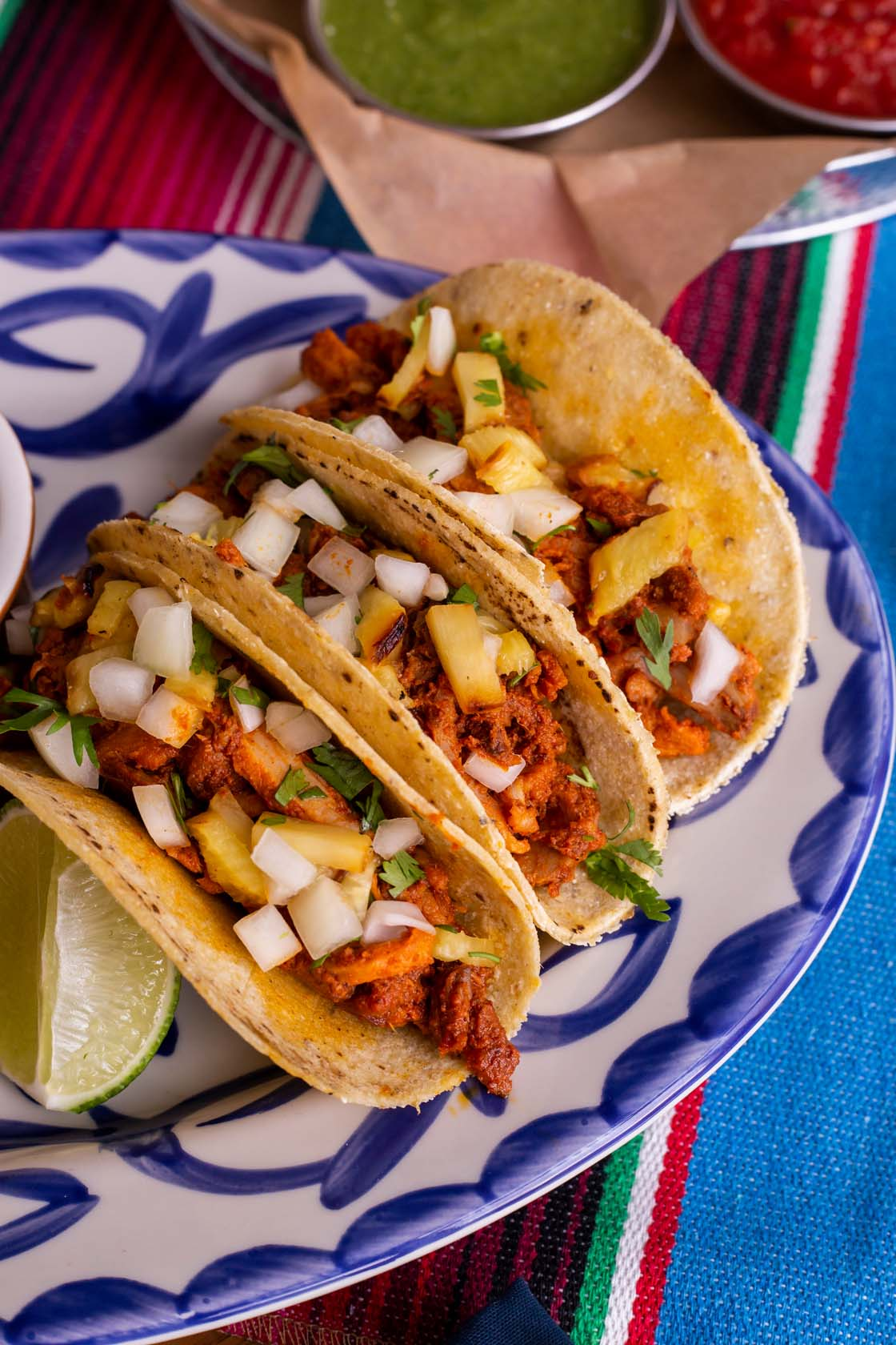 Three plated tacos filled with chicken Tinga and chopped toppings in corn tortillas.