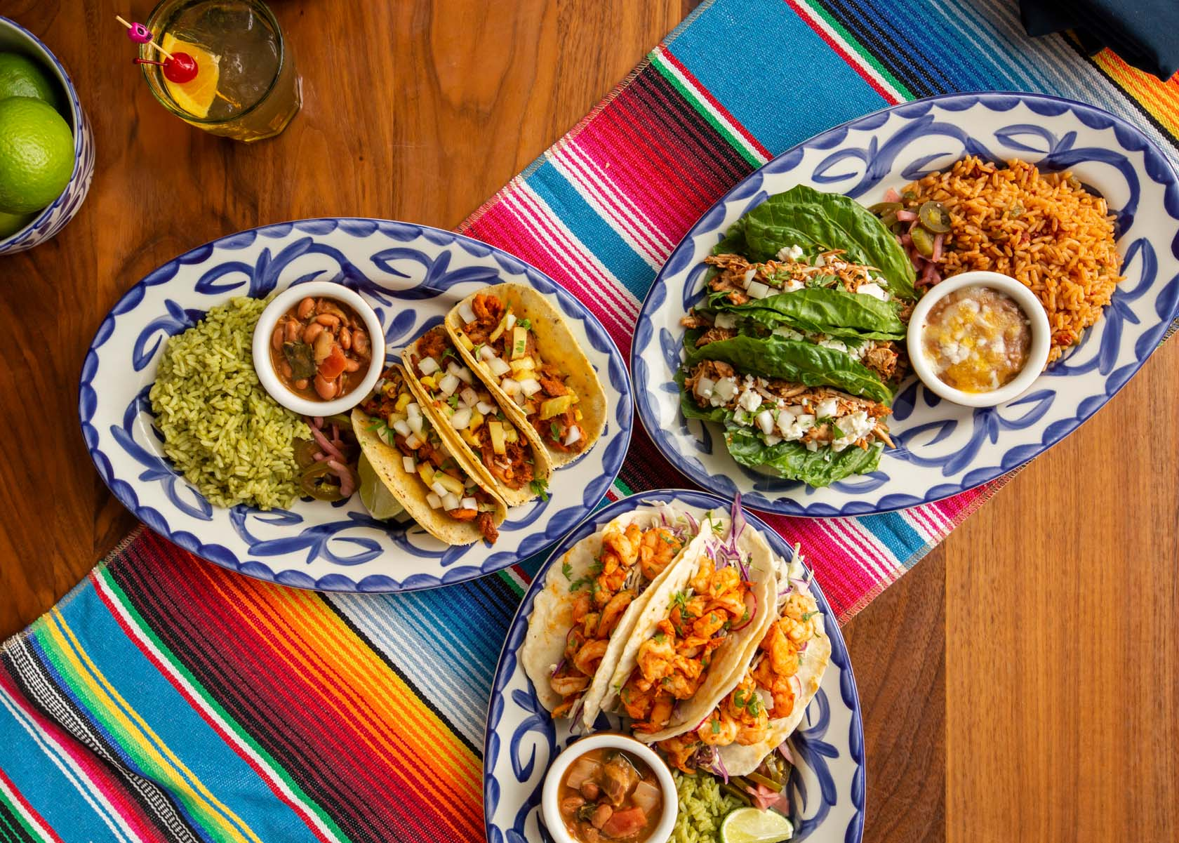 Array of plated entrees featuring tacos made with corn, flour and lettuce tortillas, plated with cilantro rice, Mexican rice and bean side dishes.