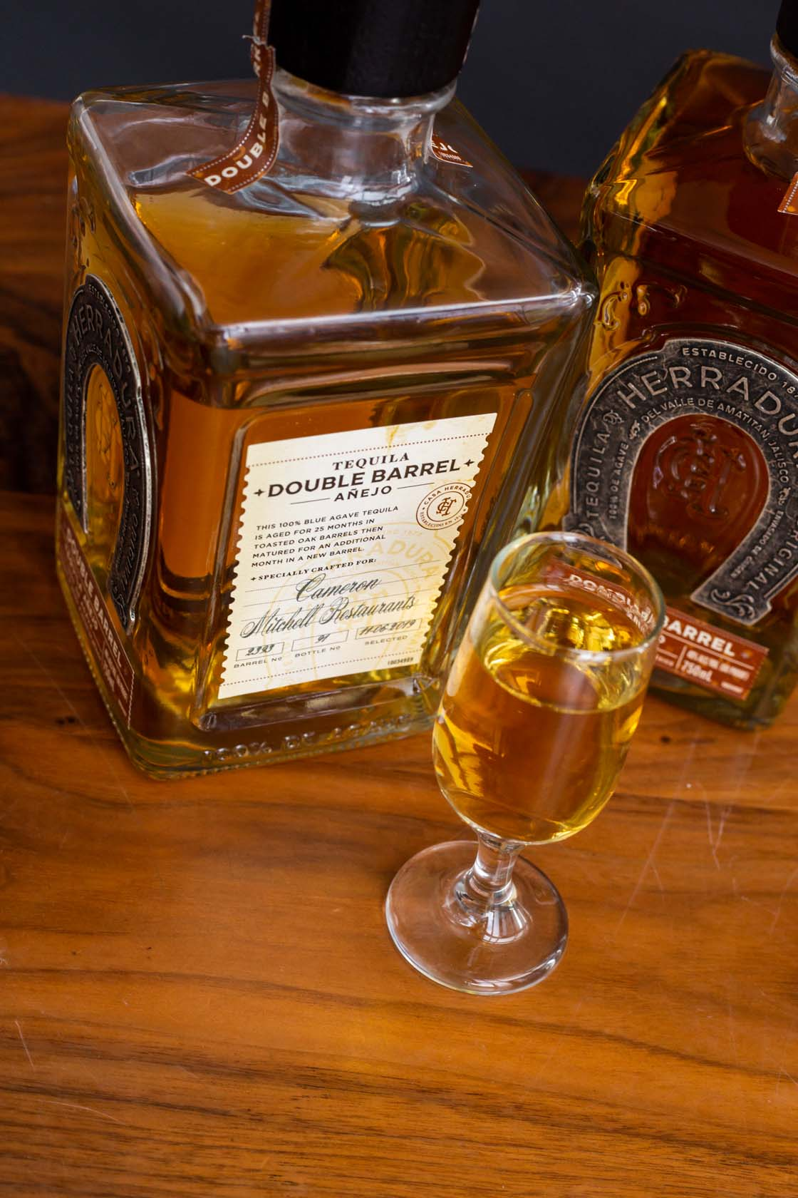 Bottle of Double Barrel Anejo, Herradura tequila with glass of tequila served neat.