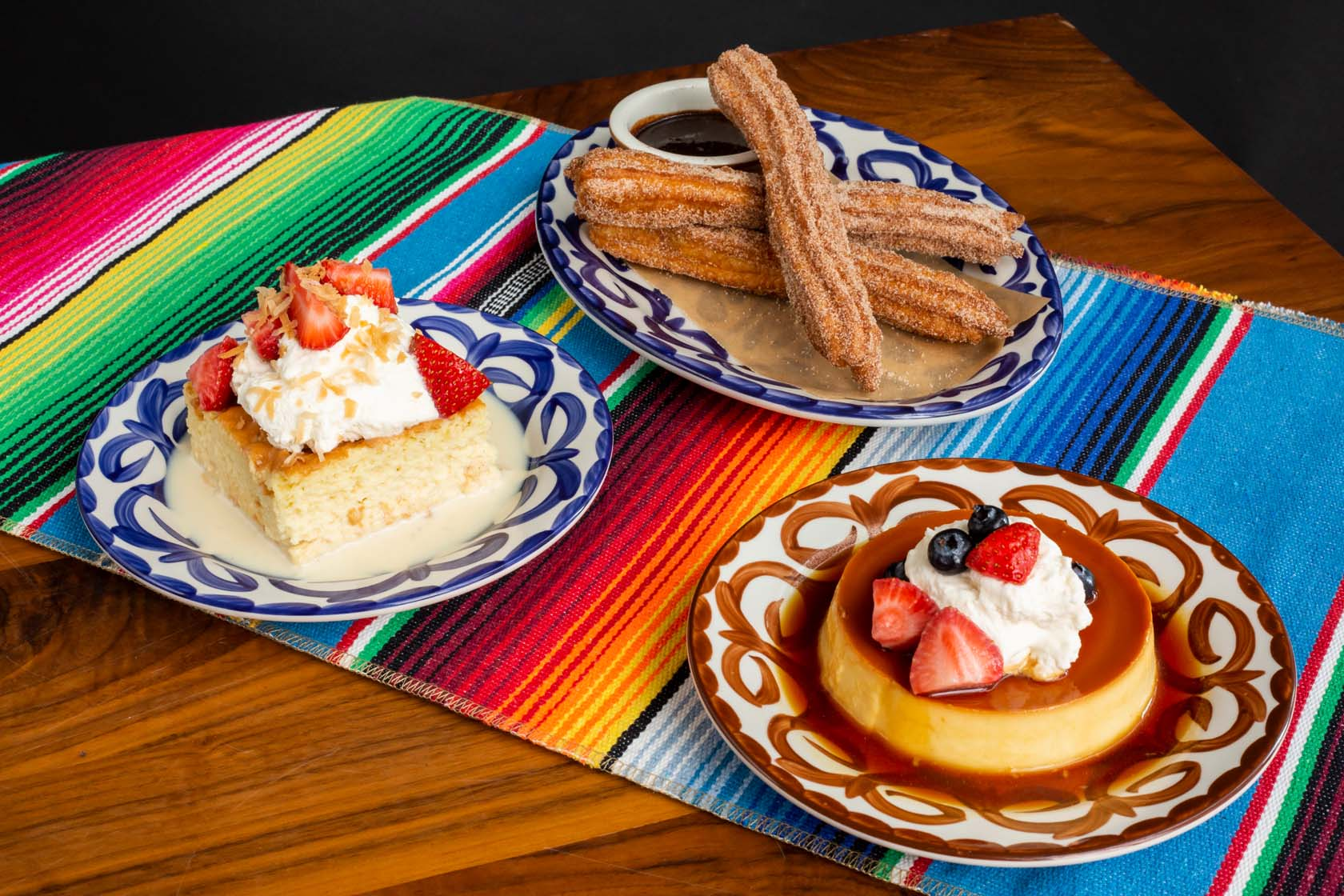 Three plated Mexican desserts - tres leches cake, churros and flan.