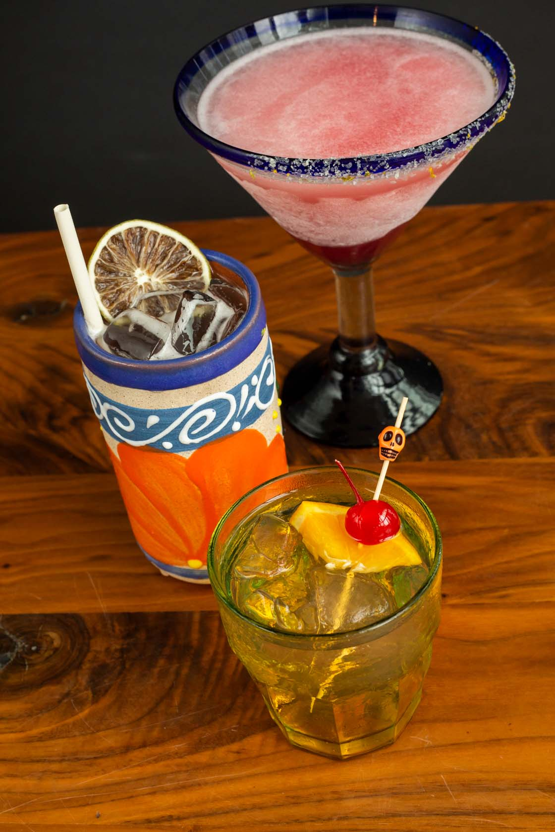 Three bar beverages - a tall pink margarita with salted rim in martini style glass; medium sized ceramic glass with iced beverage and large straw; short glass with tequila on rocks with orange and cherry garnish.