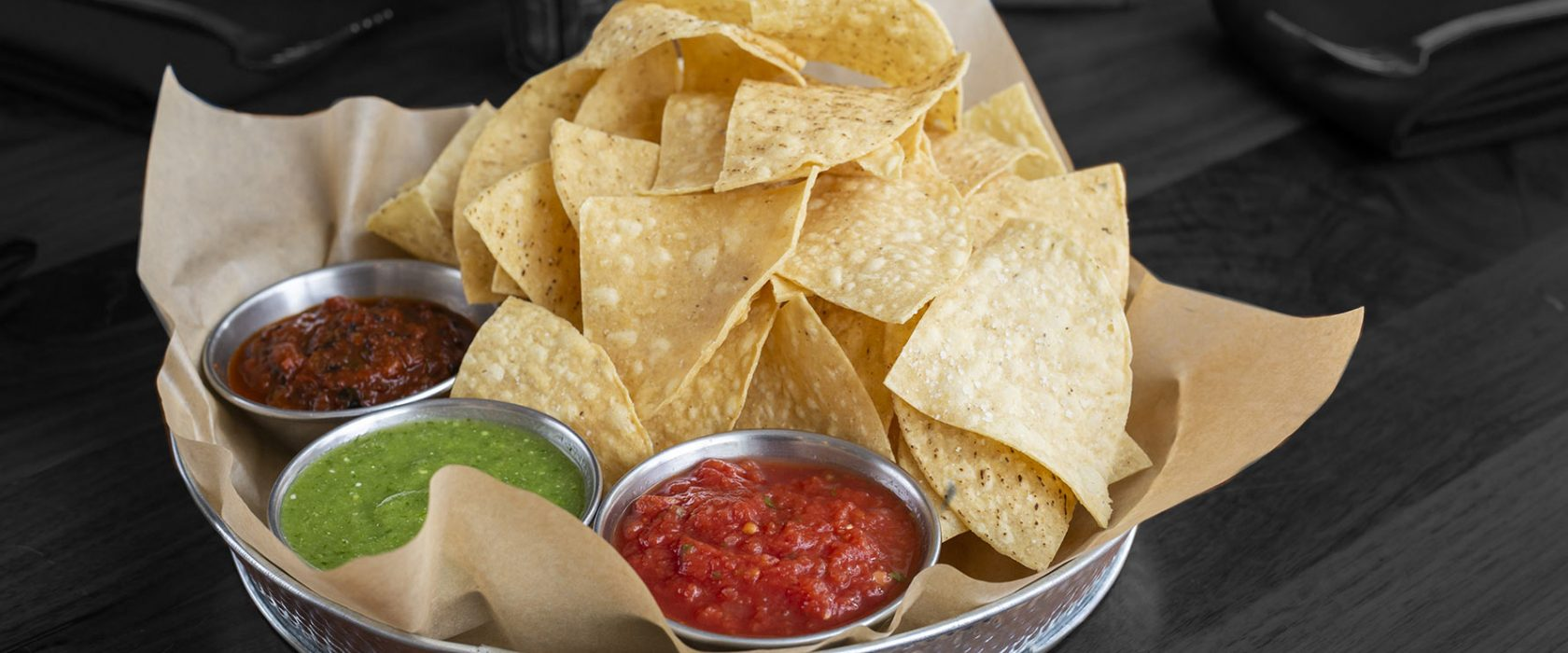 Metal bowl filled with tortilla chips and three salsas from mild to medium to hot.
