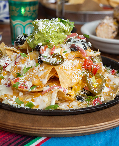 Plate of nachos appetizer with can of beer in background