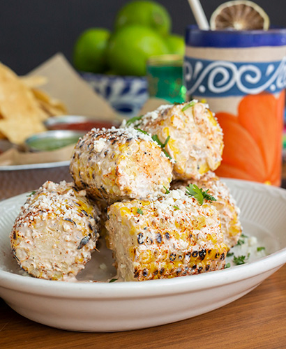 Plate of Mexican street corn with festive cocktail in background.