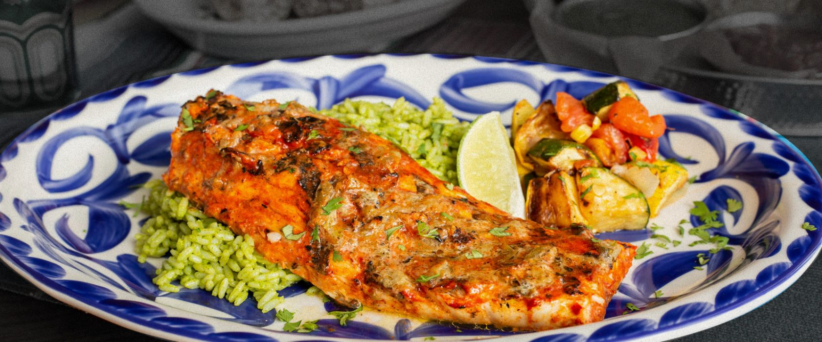Plated grilled fish over cilantro rice with wedge of lime and grilled veggies.