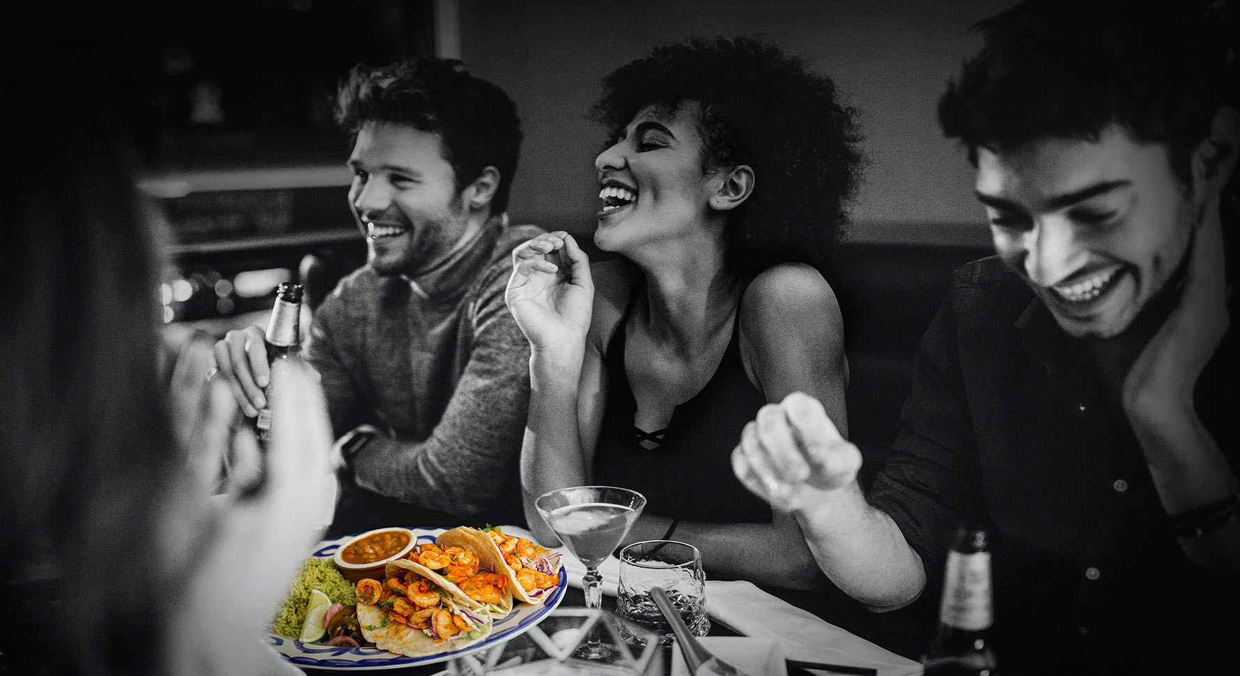 People seated in booth socializing with plate of tacos on table